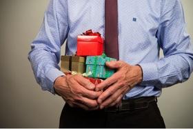Geschäftsmann mit Geschenken im Arm