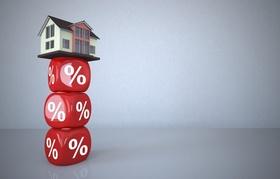 Gestapelte Würfel mit Prozentzeichen und Haus
