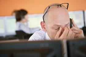 Gestresster Mann hinter PC, Brille hochgeschoben, fasst sich die Nase
