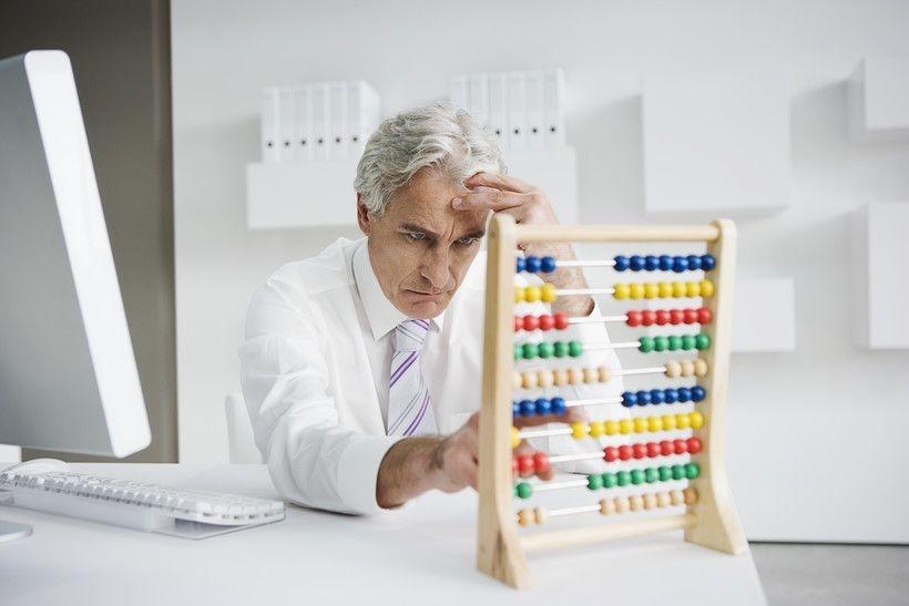 Grimmiger Mann mit Abakus in Büro