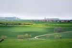 Große Freifläche mit kleinem Dorf und Windrad