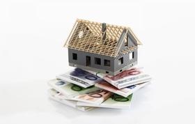 Grundgerüst Hausmodell steht auf Stapel aus Geldscheinen