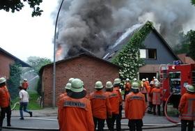 Gruppe von Feuerwehrmännern schaut auf brennendes Haus_pixabay