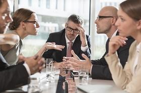 Gruppe von Leuten streitend an einem Konferenztisch