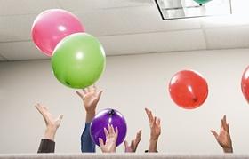 Hände die bunte Luftballons in die Höhe werfen