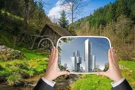 Hände halten Bild mit Hochhäusern vor Naturbild