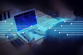 Hände tippen auf Laptop mit Vernetzungssysmbol und Binärcode