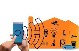 Hand die Smart Phone hält vor Haus mit WLAN Zeichen und Symbolen
