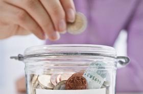 Hand gibt Münze in Einmachglas als Spardose