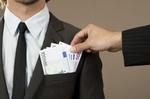 Hand greift in Anzugtasche mit Euroscheinen