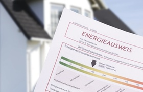 Hand haelt Energieausweis, Haus im Hintergrund