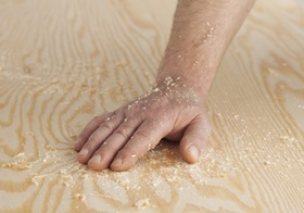 Hand liegt auf Holzfläche