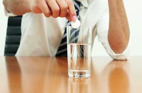 Hand löst Tablette in Glas Wasser auf