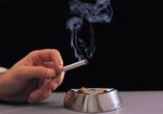 Hand mit brennender Zigarette