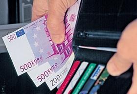 Hand mit großen Geldscheinen und Geldbeutel