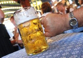 Hand mit Masskrug in Bierzelt
