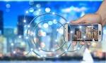 smart city-Hand die Smartphone hält vor verschwommener Silhouette einer Großstadt
