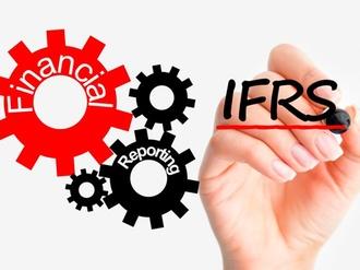 Hand schreibt IFRS neben Zahnrädchen mit Aufschrift financial reporting
