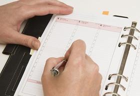 Hand schreibt in ein Terminbuch