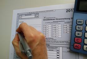 Hand schreibt in USt-Voranmeldung/Umsatzsteuer-Voranmeldung