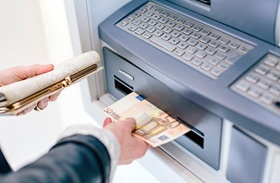 Woman's hand withdrawing 50 euro notes from cash machine