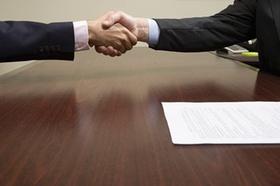 Handschlag mit Vertrag auf Tisch
