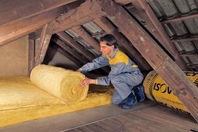 Handwerker der Isolierung auf Dachboden ausrollt
