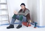 Handwerker sitzt auf Baustelle bei Pause auf Werkzeugkasten