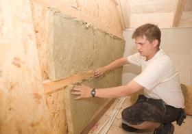 Handwerker verlegt Daemmmatten bei Hausbau