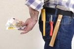 Handwerker versteckt Geld hinter seinem Rücken