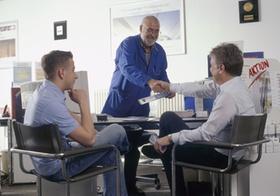 Handwerks-Meister bei Vertragsabschluss mit Kunden im Buero