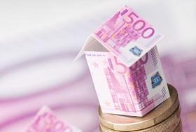 Haus aus Geldscheinen auf Euromünze