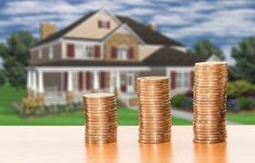 Haus im Hintergrund Stapel Münzen ansteigend