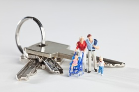 A young family of miniature figurines standing next to house keys on a key ring