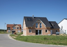 Hausbau_Haus mit Gerüst auf der grünen Wiese