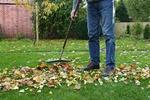 Hausmeister beim Blätter zusammenfegen