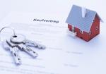 Hausmodell und Schluessel auf Kaufvertrag