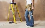 Heimwerkerin steht mit Werkzeug vor Leiter