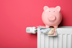 Savings concept. Piggy bank and money on heating radiator with temperature regulator on pink backgro