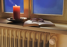 Heizkoerper unter altem, undichtem Fenster, Kerze, Buch