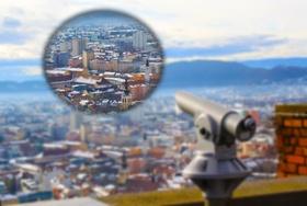 Immobilienblase über Stadt durch Fernglas