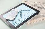iPhone und iPad liegen auf Finanzzeitung