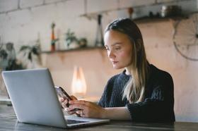 Jobsuche: Frau schaut vor Laptop auf ihr Smartphone
