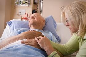 jüngere Frau sitzt am Bett eines alten Mannes und hält die Hand