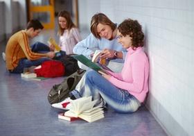 Jugendliche Schueler sitzen im Gang