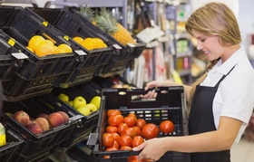 Junge Erwachsene Mitarbeiterin die im Supermarkt Waren einräumt