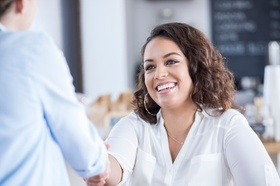 Young businesswoman shakes a client or customer's hand. They are meeting in a local cafe.