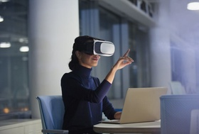 Businesswoman using virtual reality simulator at laptop in office