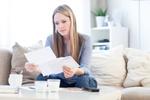junge Frau blickt besorgt auf Briefe