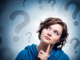 Junge Frau blickt ratlos fragend, Fragezeichen im Hintergrund